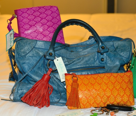 {Fuchsia Neem Clutch, small Orange Neem Clutch & Red Tassel Key Ring shown on Blue Balenciaga Bag}